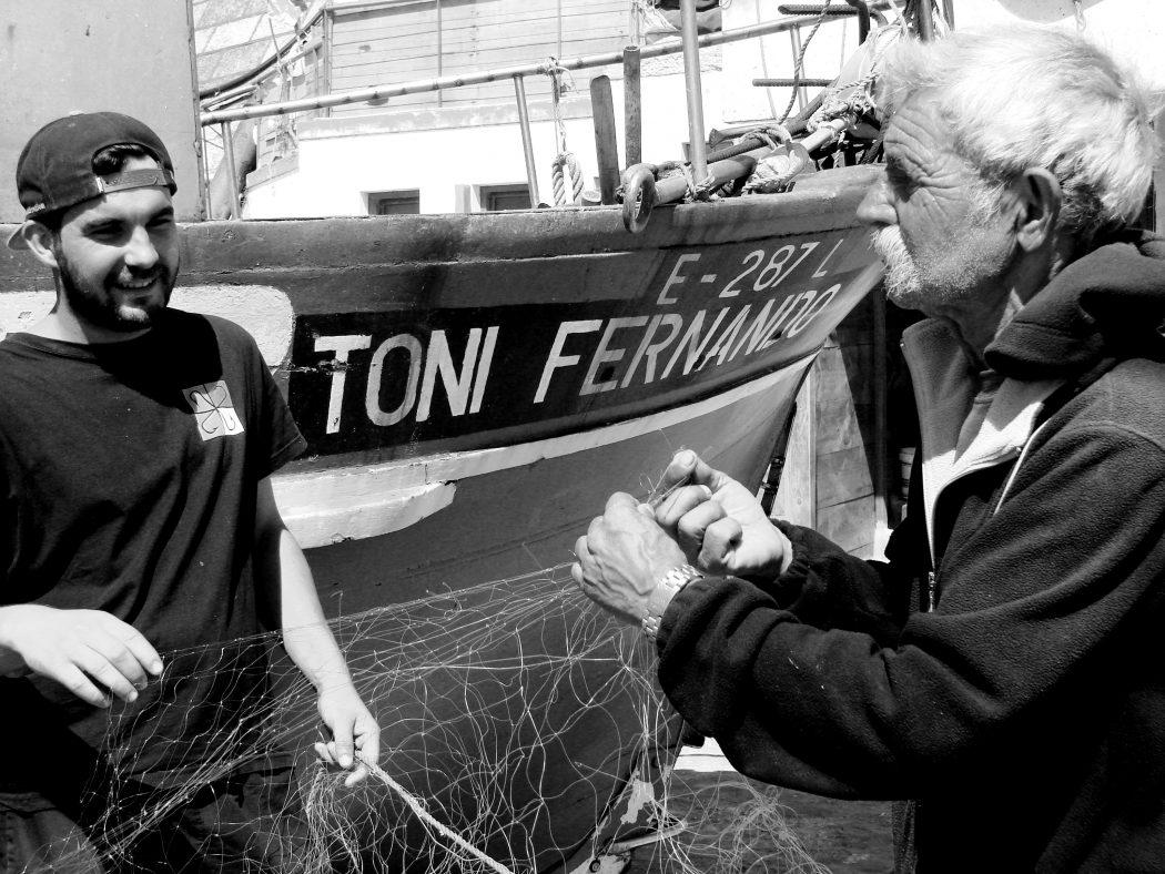 Encontro de gerações, na fotografia e na faina diária do barco (de madeira) Tony Fernando. Aqui Aníbal Franco Alberto – também conhecido por Faneca - ainda pode ensinar a Bruno Morais, de 22 anos, as antigas artes, dando continuidade a uma tradição tão antiga como valiosa, património imaterial da Ericeira.